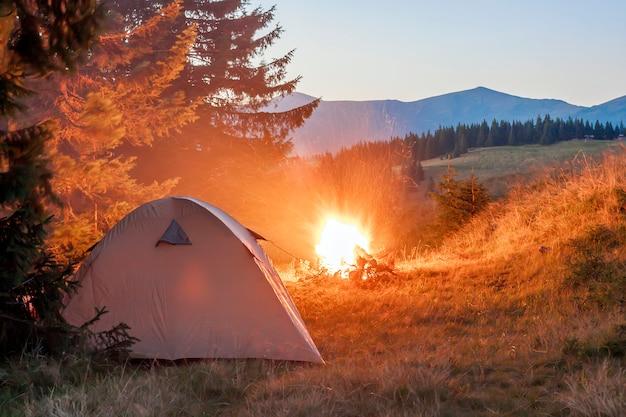 Turystów namiot w górach wieczorem z ogniskiem w pobliżu błyszczy