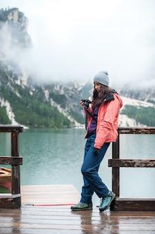 Turystyczna dziewczyna bierze fotografię na kamerze przy jeziornym brice, włoski dolomit