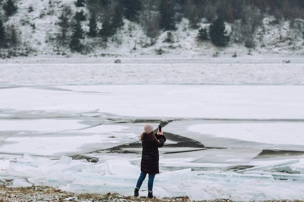 Turystyczna dziewczyna podróżująca po zamarzniętej rzece i robienie zdjęć zimowy krajobraz. dziewczyna na ferie zimowe.