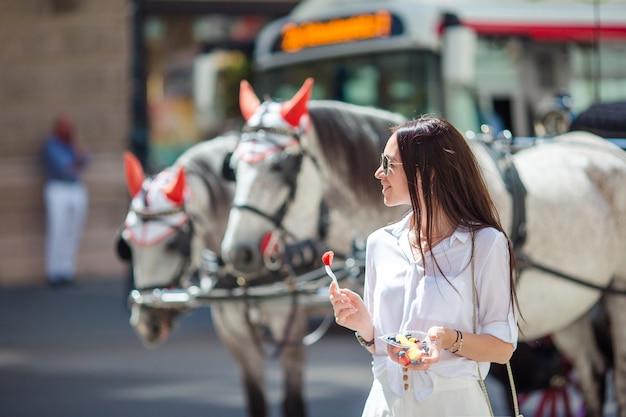 Turystyczna dziewczyna spacerująca po wiedniu i patrząc na piękne konie w powozie