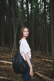Turystyczna dziewczyna w białej koszulce z plecakiem trzymając smartfon w górskim lesie