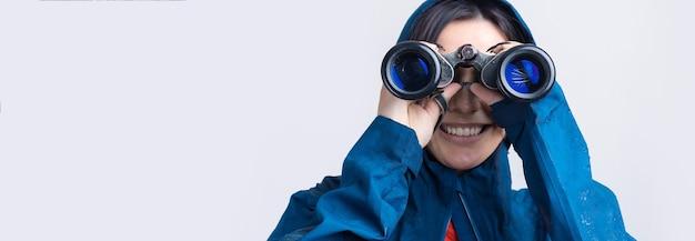 Turystyczna dziewczyna w niebieskim płaszczu przeciwdeszczowym trzyma w rękach lornetkę i patrzy w dal, szpiedzy.