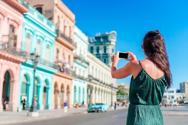 Turystyczna dziewczyna w popularnym terenie w hawańskim, kuba. młoda kobieta podróżnika ono uśmiecha się szczęśliwy.