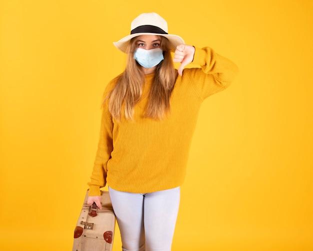 Turystyczna dziewczyna z maską medyczną, epidemia koronawirusa covid-19. pojęcie odwołanych podróży. turysta nie może wyjechać z powodu pandemii.
