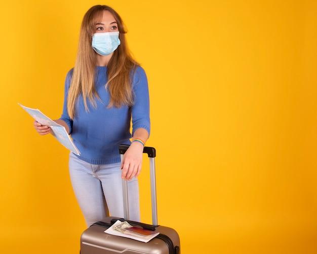 Turystyczna dziewczyna z maską medyczną, walizką, paszportem i biletami lotniczymi oraz mapą, lot został odwołany przez covida-19
