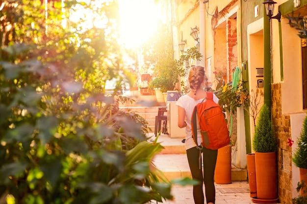 Turystyczna dziewczyna z plecakiem idzie ulicą