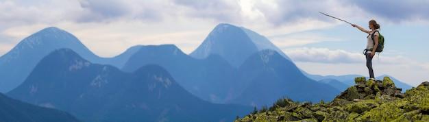 Turystyczna dziewczyna z plecakiem wskazuje kijem przy mgłowym pasmem górskim