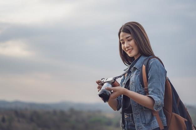 Turystyczna kobieta bierze fotografię z jej kamerą w naturze