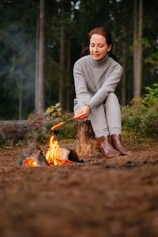 Turystyczna kobieta na kempingu gotuje mięso na ognisku w lesie koncepcja wędrówki ekoturystycznej