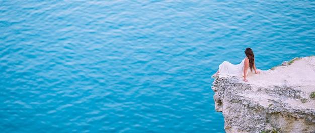 Turystyczna kobieta na zewnątrz na skraju urwiska nad morzem