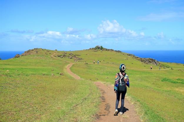 Turystyczna kobieta odwiedzająca wioskę orongo, historyczne centrum ceremonialne na wyspie wielkanocnej, chile