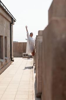 Turystyczna kobieta podnosząca rękę, ciesząca się widokiem panoramicznym