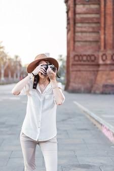 Turystyczna kobieta podróżująca z aparatem. podróżniczka spacerująca po ulicach barcelony robiąca zdjęcia