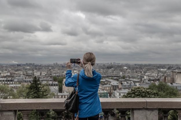Turystyczna kobieta robi zdjęcie miasta w pochmurną pogodę z aparatu w telefonie komórkowym
