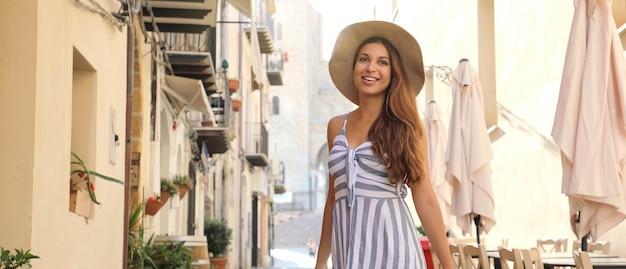 Turystyczna kobieta spaceru na starym mieście w cefalu na sycylii, we włoszech