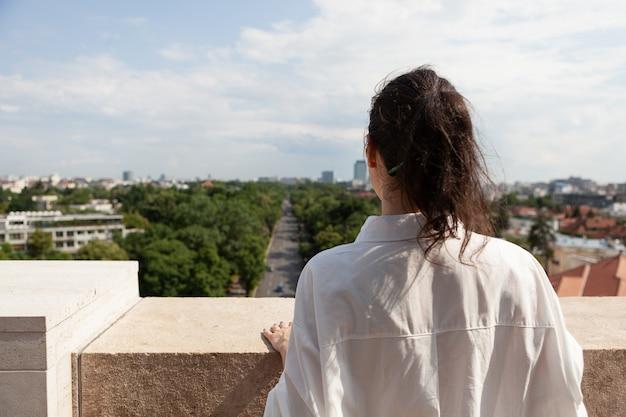 Turystyczna kobieta stojąca na tarasie wieży ciesząc się letnimi wakacjami