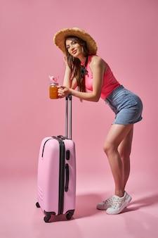Turystyczna kobieta w letnich ubraniach z walizką na różowym tle