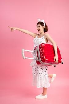Turystyczna kobieta w letnich ubranie z walizką podróży na różowo