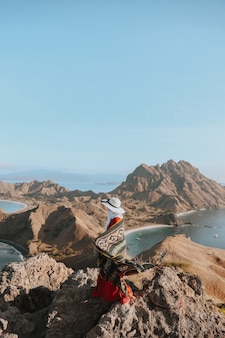 Turystyczna kobieta w letnim kapeluszu, ciesząc się wakacjami na szczycie wzgórza na wyspie padar labuan bajo