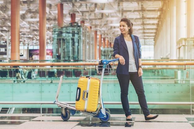 Turystyczna kobieta w lotniskowym terminal z bagażem