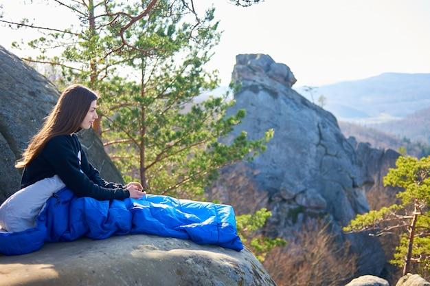 Turystyczna kobieta w śpiworach na dużych skałach