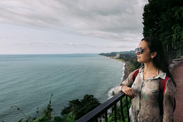 Turystyczna kobieta w zielonej pelerynie, georgia. piękne wybrzeże morza czarnego