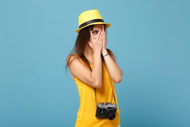Turystyczna kobieta w żółtych letnich ubraniach i kapeluszu z aparatem fotograficznym na niebiesko