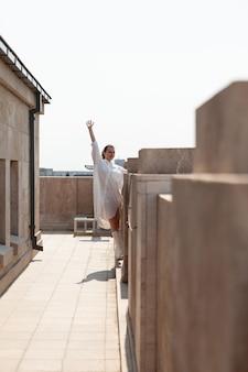 Turystyczna kobieta wznosząca rękę, ciesząca się widokiem metropolii z panoramicznej wieży