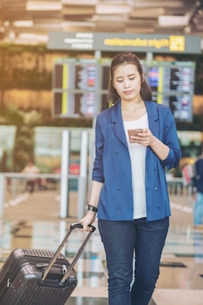Turystyczna kobieta z bagażem na lotnisku