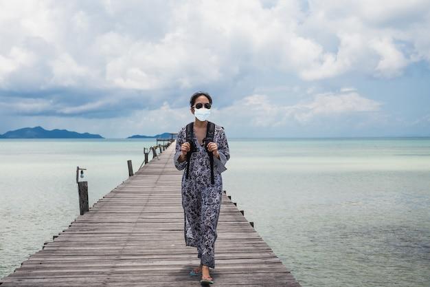 Turystyczna kobieta z maską ochronną na drewnianym moście z widokiem na ocean.