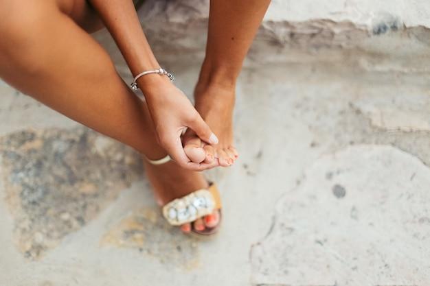 Turystyczna kobieta z obolałymi stopami i pęcherzami sprawdza swoje obolałe stopy.