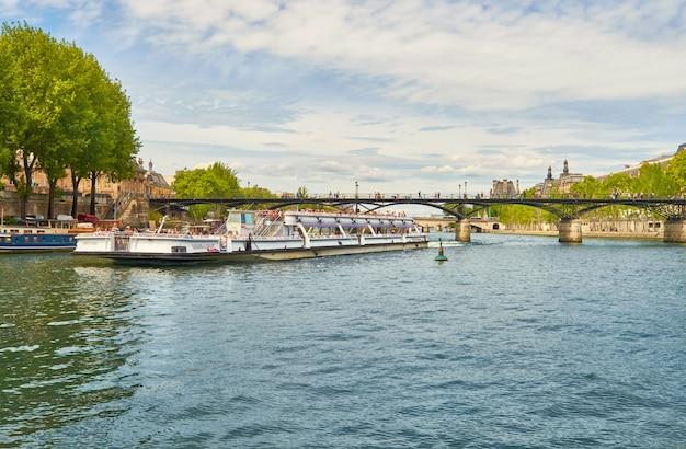 Turystyczna łódź przechodzi pod pont des arts na sekwany w paryż, francja
