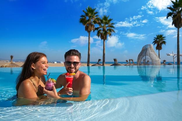 Turystyczna para ma skąpanie w nieskończoność basenie na miejscowości nadmorskiej z koktajlami