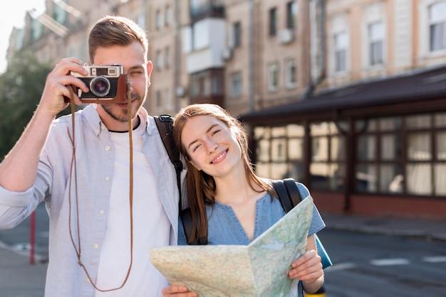 Turystyczna para pozuje na zewnątrz z aparatem i mapą