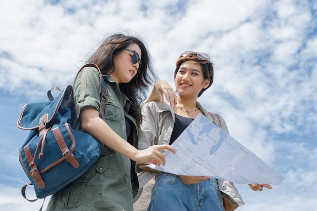 Turystyczna para używa mapę dla znalezienia lokaci pod niebieskim niebem
