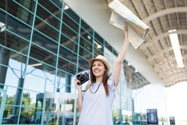 Turystyczna podróżniczka trzyma retro aparat fotograficzny w stylu vintage, papierową mapę macha ręką na powitanie, spotkanie z przyjacielem i złap taksówkę na lotnisku