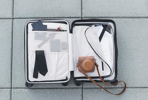 Turystyczna walizka siedzi na ziemi