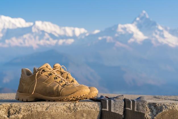 Turystyczne buty trekkingowe ze skarpetami z ośnieżonymi szczytami annapurna na tle. trekking górski i turystyka, podróże i turystyka koncepcja. zdjęcie stockowe z bliska.