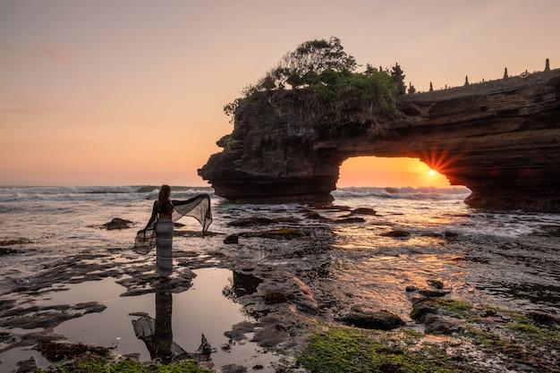 Turystyczne pozy nad brzegiem morza ze słońcem przez skalisty klif o zachodzie słońca