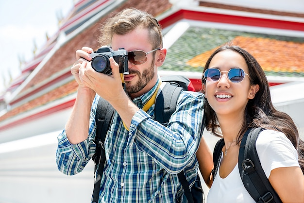 Turystyczni par backpackers bierze fotografie podczas gdy podróżujący w bangkok tajlandia