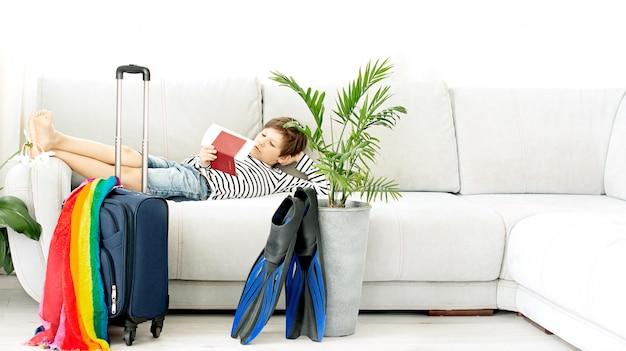 Turystyczny chłopiec z walizką i płetwami zostaje w domu