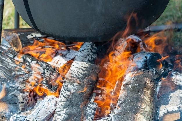 Turystyczny czarny kocioł z jedzeniem na ognisku, gotowanie w wędrówce. przygotowanie pilawu lub zupy na ogniu