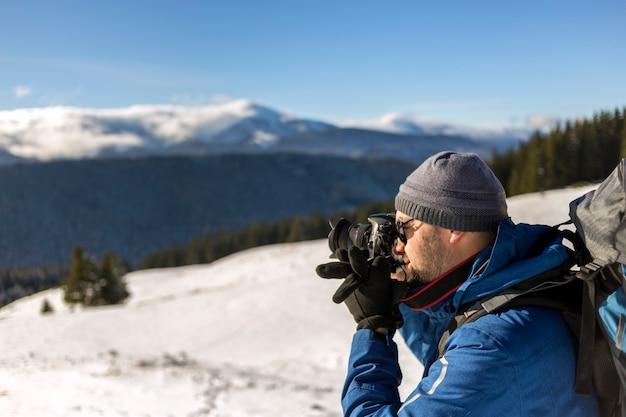 Turystyczny fotograf turystyczny turysta w ciepłej odzieży z plecakiem i aparatem fotografujący śnieżną dolinę i leśne szczyty górskie krajobraz pod błękitnym niebem w słoneczny zimowy zimny dzień.