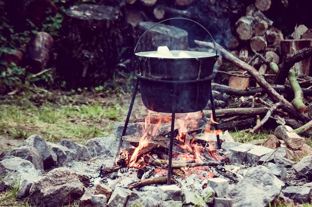 Turystyczny kociołek gotującego się jedzenia nad ogniskiem