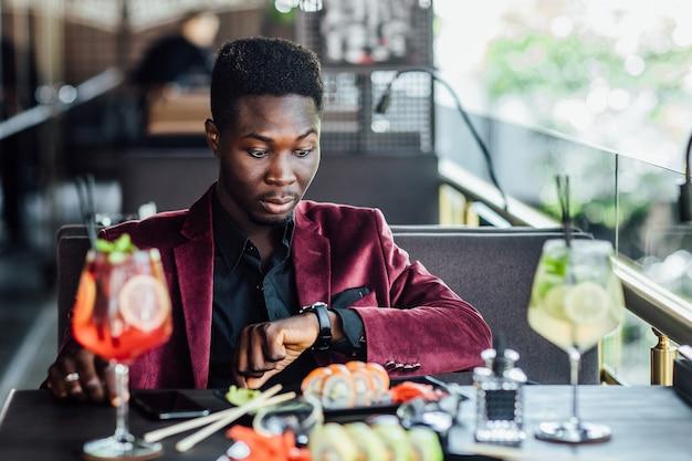 Turystyczny mężczyzna jedzenie azjatyckie jedzenie ulicy lokalnej kawiarni, patrząc na zegarek.