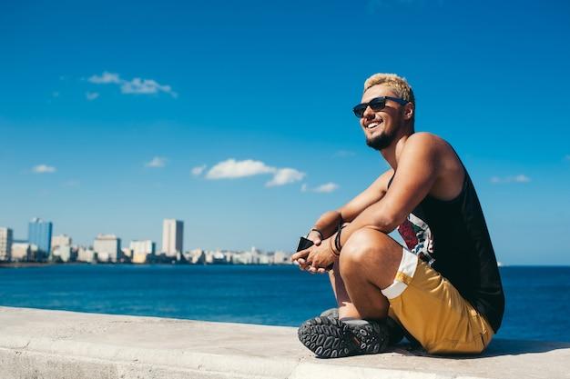 Turystyczny mężczyzna siedzący na kamieniu, uśmiechający się i pozujący na tle błękitnego morza