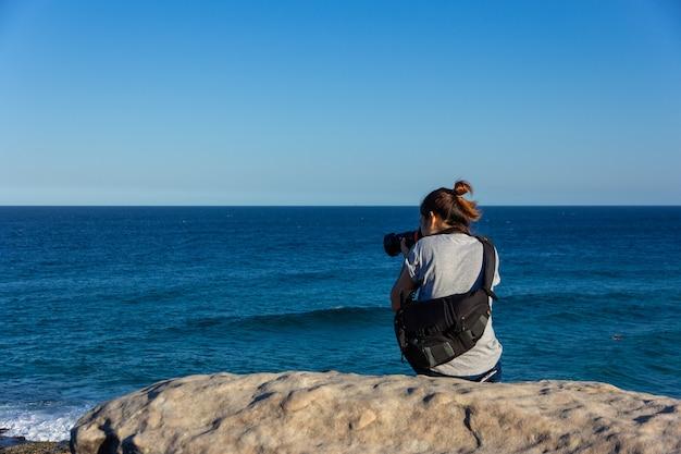Turystyczny obsiadanie na krawędzi rockowej falezy i bierze fotografię błękitnego ocean