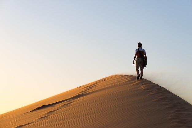 Turystyczny odprowadzenie na piasek diunach przy sossusvlei, namib pustynia. podróżujący ludzie, przygoda i wakacje w afryce.