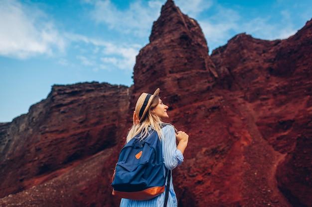 Turystyczny odprowadzenie na rewolucjonistki plaży w akrotiri, santorini wyspa, grecja. kobieta wycieczkowicz podróżuje z plecakiem patrzeje skały