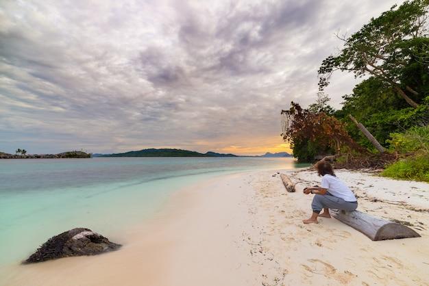 Turystyczny ogląda zmierzch na plaży w dalekich wysp togean